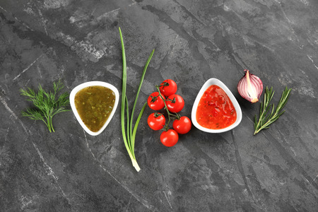 Composition with tasty sauces on grey textured background