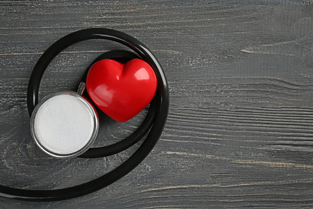 Stethoscope with small heart on dark wooden background