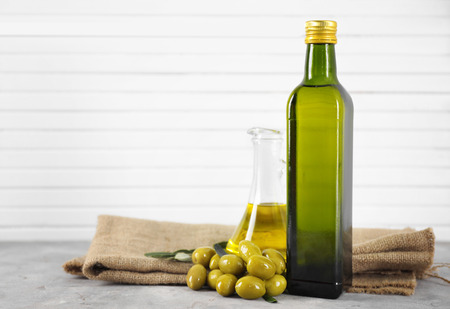 Composition with olive oil in bottle and jug on table