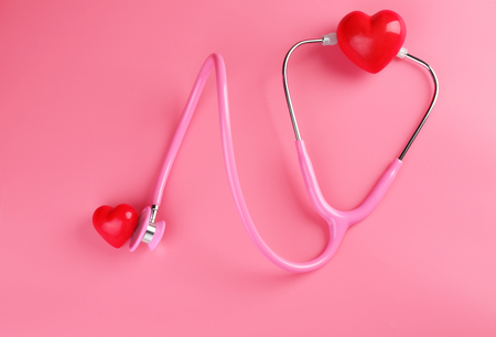 Stethoscope with small hearts on color background