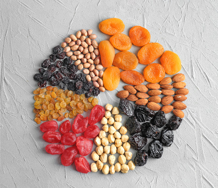 Different kinds of nuts and dried fruits on table Imagens