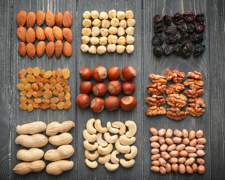 Different kinds of nuts and dried fruits on wooden background, top view 스톡 콘텐츠