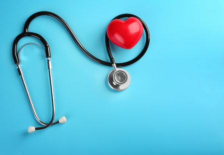 Stethoscope with small heart on color background