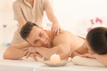 Happy young couple having massage in spa salon Foto de archivo