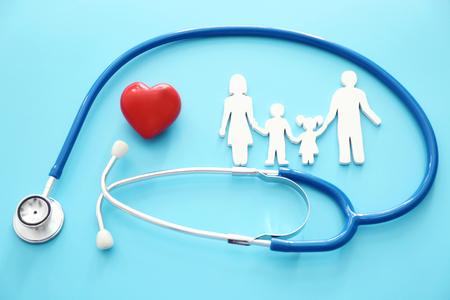 Figura familiar, corazón rojo y estetoscopio sobre fondo de color. Concepto de cuidado de la salud Foto de archivo
