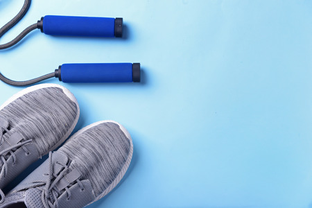 Flat lay composition with sneakers and jumping rope on color background. Gym workout