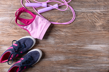 Flat lay composition with sneakers, sport top and jumping rope on wooden background. Gym workout Stock fotó