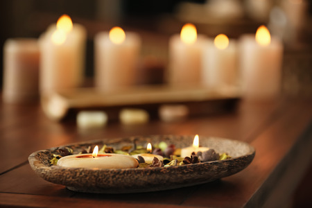 Burning candles on table in spa salon