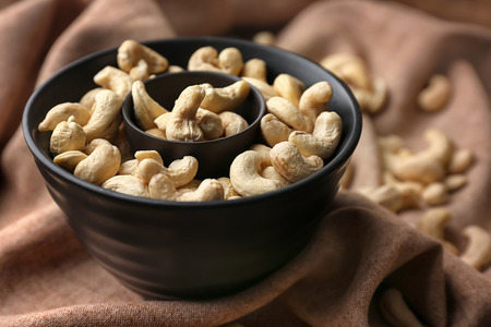 Bowl with tasty cashew nuts on table