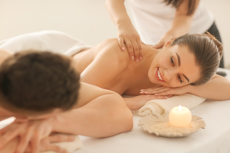 Happy young couple having massage in spa salon Stock Photo