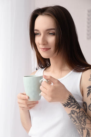 Young beautiful woman drinking coffee at home in morning