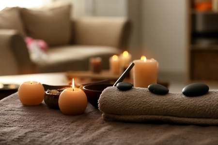 Burning candles, towel and stones on massage table in spa salon
