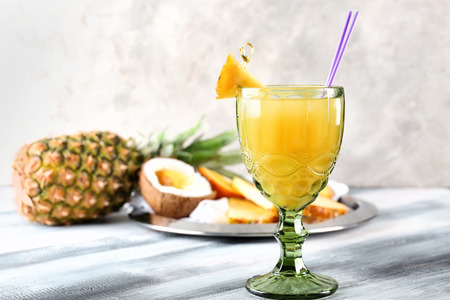 Glass of sweet pineapple juice on table