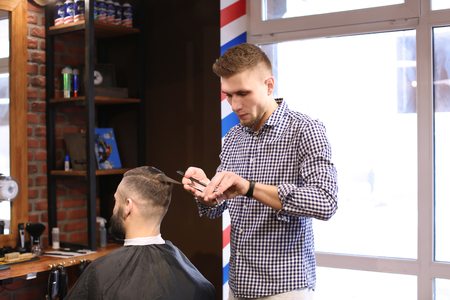 Professional barber working with client in hairdressing salon Stock Photo