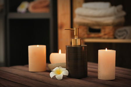 Burning candles and cosmetic product on table in spa salon