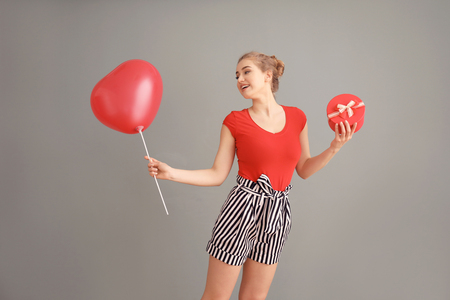Beautiful young woman with gift box and heart-shaped balloon on color background Stok Fotoğraf