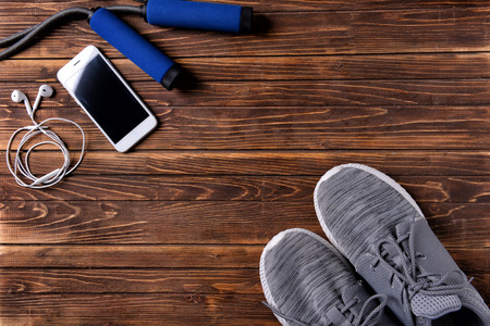 Flat lay composition with sneakers, smartphone and jumping rope on wooden background. Gym workout 版權商用圖片