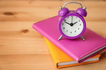 Alarm clock and notebooks on wooden table. Time management concept Stock Photo