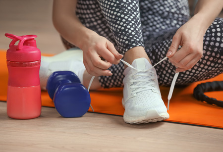 Young woman tying shoelaces on floor in gym, closeup
