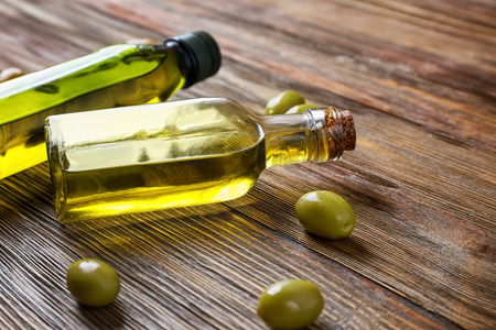 Bottles with olive oil on wooden table