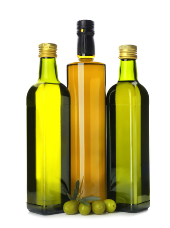 Bottles with oil and olives on white background