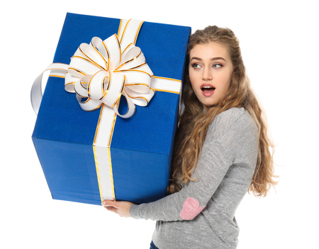Surprised young woman with big gift box on white background