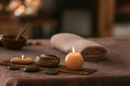 Burning candles, stones and towel on massage table in spa salon