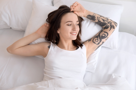 Young beautiful woman lying on bed in morning 写真素材 - 113902855