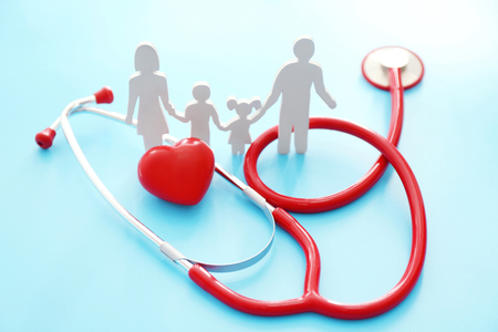 Family figure, red heart and stethoscope on color background. Health care concept Stock Photo