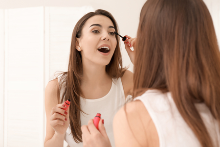 Morning of beautiful young woman applying makeup at home