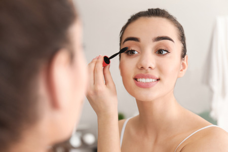 Young beautiful woman applying makeup in morning