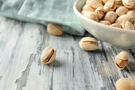 Pistachio nuts on wooden table, closeup