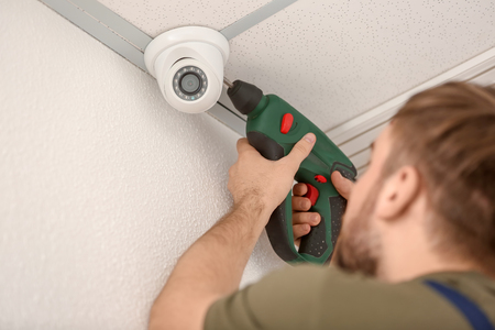 Electricista instalando cámara de seguridad en interiores