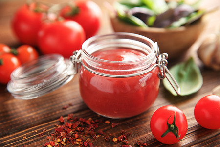 Delicious red sauce in glass jar and ingredients on table