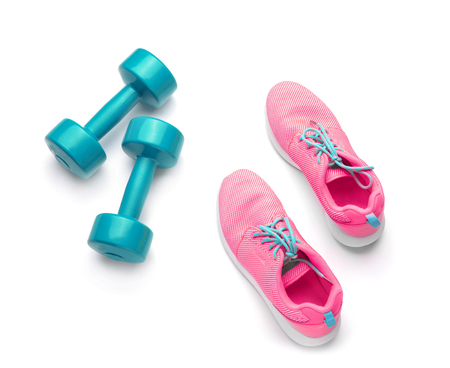 Dumbbells and sneakers on white background