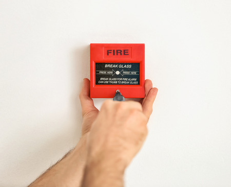 Electrician installing fire alarm unit on wall