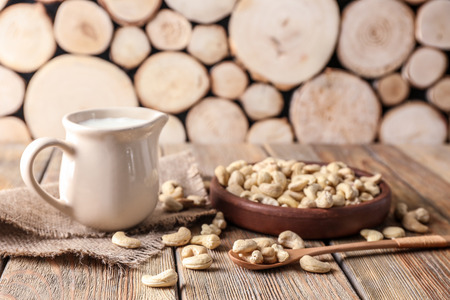 Plate with tasty cashew nuts and jug of milk on wooden table