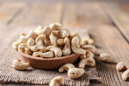 Plate with tasty cashew nuts on wooden table