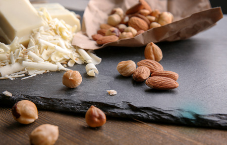 Slate plate with white chocolate curls and nuts on table