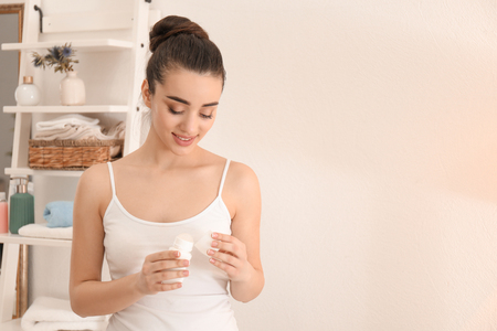 Beautiful young woman using deodorant in morning
