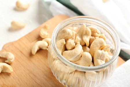 Glass jar with fresh cashew nuts on table, closeup