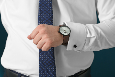 Man looking at his watch, closeup. Time management concept