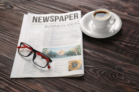Newspaper with glasses and cup of coffee on wooden table 스톡 콘텐츠