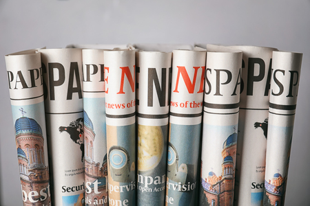 Rolled newspapers on grey background