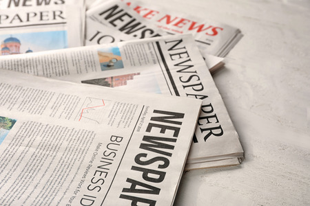Newspapers on white wooden background 免版税图像