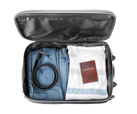 Open suitcase with packed things on white background, top view