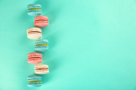 Delicious macarons on color background