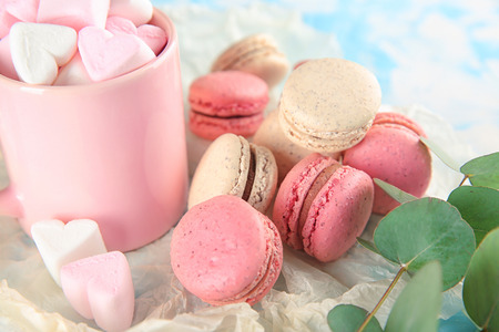 Tasty macarons and mug with marshmallows on table