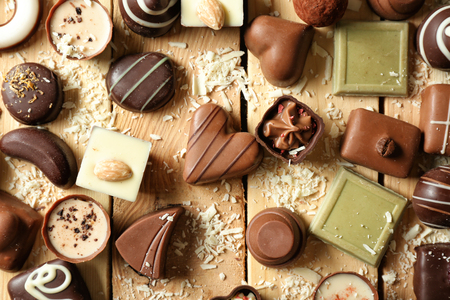 Different tasty chocolate candies on wooden table