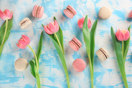 Flat lay composition with tasty macarons and tulips on color background